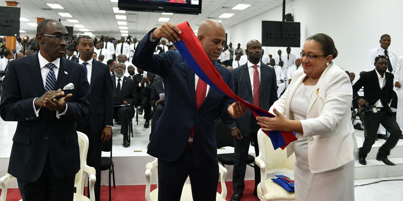 AFP - Le président haïtien Michel Martelly s'apprête à remettre son écharpe présidentielle.