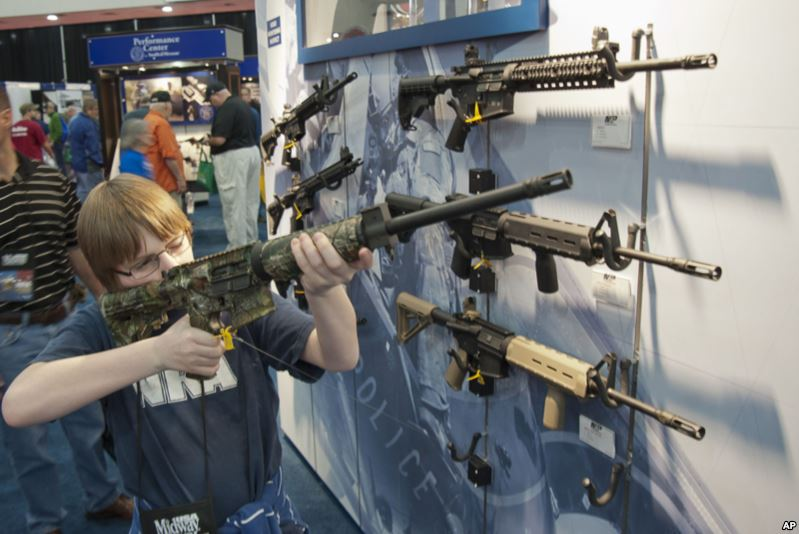 Un garçon essaie une arme pendant la convention annuelle de la National Rifle Association, à Houston, en 2013. Photo Associated Press