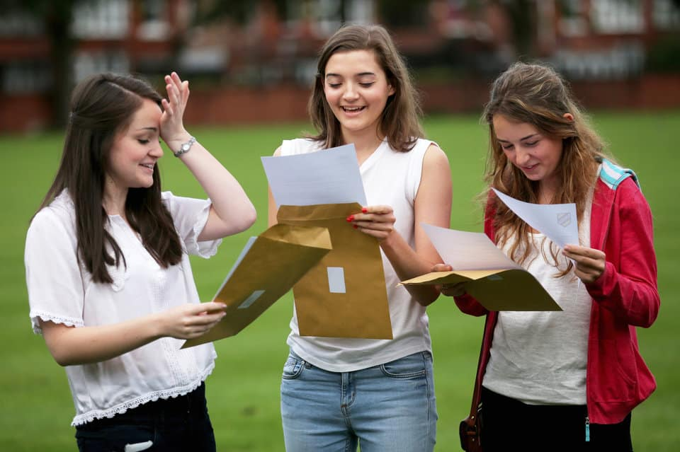 MANCHESTER, ENGLAND - AUGUST 15:  (EDITORS NOTE: This image has been manipulated to remove personal details)  Withington Independent Girls School pupils Helen Carrington (L), 18, Eliza Rooney, 17 and Rebecca Gray (R), 18, celebrate achieving four A*  each in their A level exams on August 15, 2013 in Manchester, England. Over 300,000 teenagers are getting the results of their A-levels today as university admissions body UCAS said a record number of students have been accepted by UK universities.  (Photo by Christopher Furlong/Getty Images)