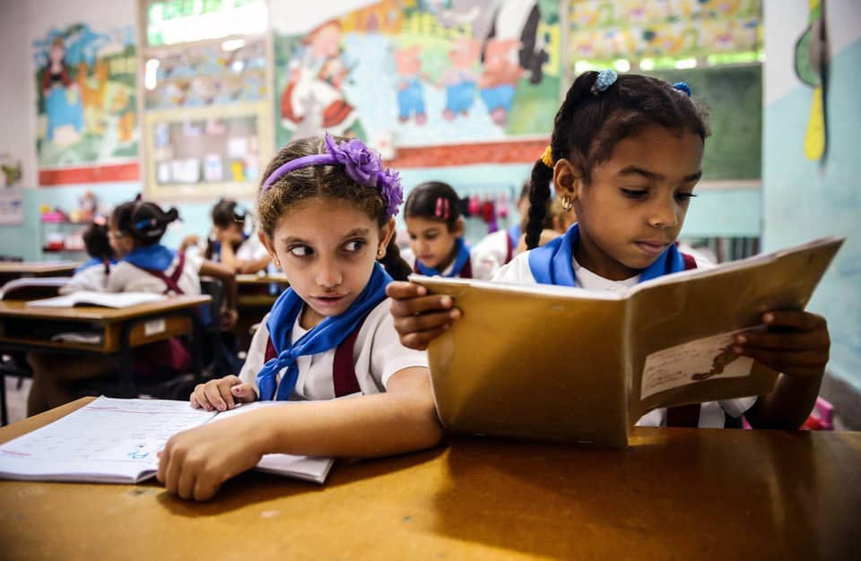 Cuban schoolgirls read during class, on November 13, 2012, in Havana.      AFP PHOTO        (Photo credit should read STR/AFP/Getty Images)