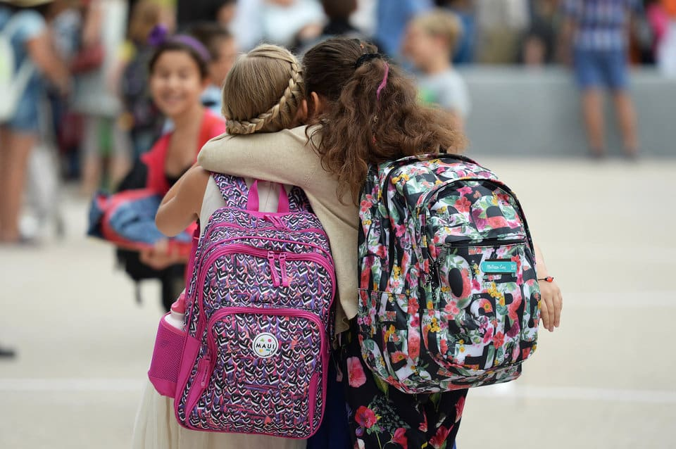Girls hug each other outside the European school of Strasbourg (Ecole Europeenne de Strasbourg) in Strasbourg, eastern France, on September 1, 2015, the first day of the new school year. AFP PHOTO / PATRICK HERTZOG        (Photo credit should read PATRICK HERTZOG/AFP/Getty Images)
