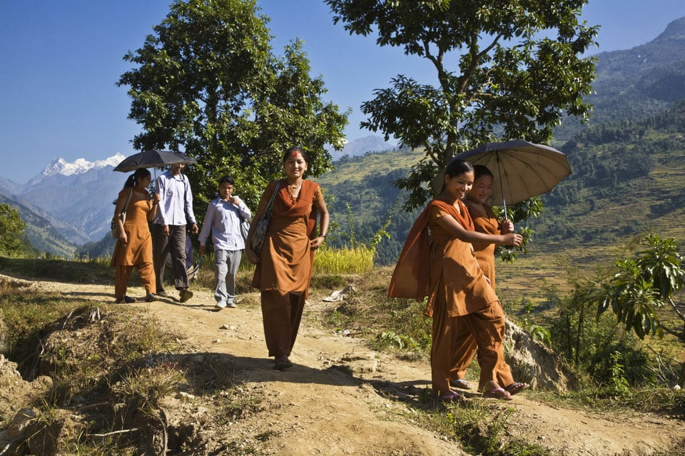 School Girls In Orange Uniforms Walk To School Along A Trail, Around Manaslu Trek, Nepal . (Photo By: Education Images/UIG via Getty Images)