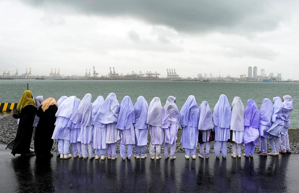 Sri Lankan Muslim school girls stand on the edge of a sea port in Colombo on May 20, 2013, after travelling from their town of Kalmunai, over 370 kilometres (231 miles)  east of the capital Colombo. Work on a USD 500-million new container terminal is nearing completion at Colombo which is a key transhipment hub for Indian cargo. AFP PHOTO/ LAKRUWAN WANNIARACHCHI        (Photo credit should read LAKRUWAN WANNIARACHCHI/AFP/Getty Images)