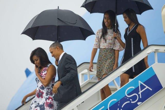 Le président américain, tout sourire, a descendu les marches de Air Force One tenant un parapluie, avec sa femme Michelle et leurs deux filles, Malia et Sasha. Photo AP