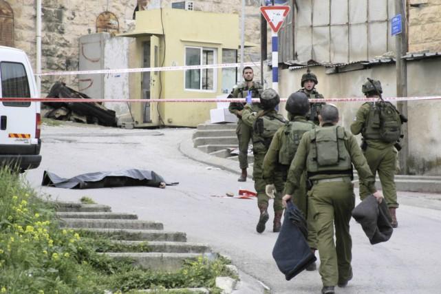 Des soldats israéliens sont vus à proximité du corps d'un Palestinien tué après avoir attaqué au couteau des soldats à Hébron, le 24 mars. L'armée israélienne a arrêté un de ses hommes soupçonné d'avoir achevé l'assaillant présumé, alors qu'il était étendu au sol. Photo AP