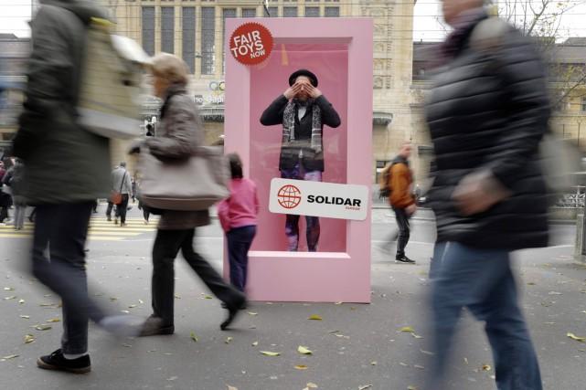 Les passants étaient invités à se faire photographier à côté de la boîte géante contenant un Ken en veste noire et collants bariolés installée devant la gare de cette ville suisse. Photo AFP