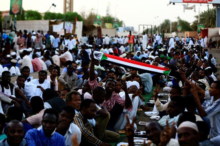 Des manifestants soudanais brandissant des drapeaux sont rassemblés devant le QG de l'armée à Khartoum, le 19 mai 2019