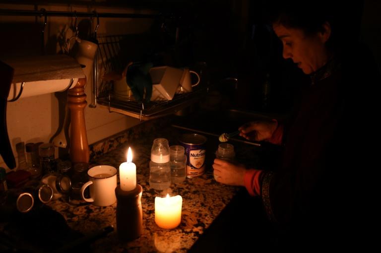 Une femme allume des bougies chez elle à Montevideo le 16 juin 2019 lors d'une panne d'électricité
