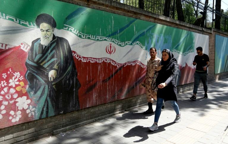 Des passants devant une fresque sur le mur de l'ancienne ambassade américaine montrant l'ayatollah Rouhollah Khomeiny, fondateur de la République islamique d'Iran, à Téhéran le 22 juin 2019