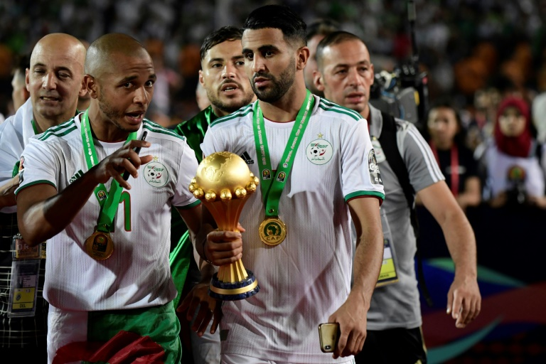 Les Algériens Riyad Mahrez (d) et Yacine Brahimi avec le trophée après la vicotire en finale de la CAN le 19 juillet 2019