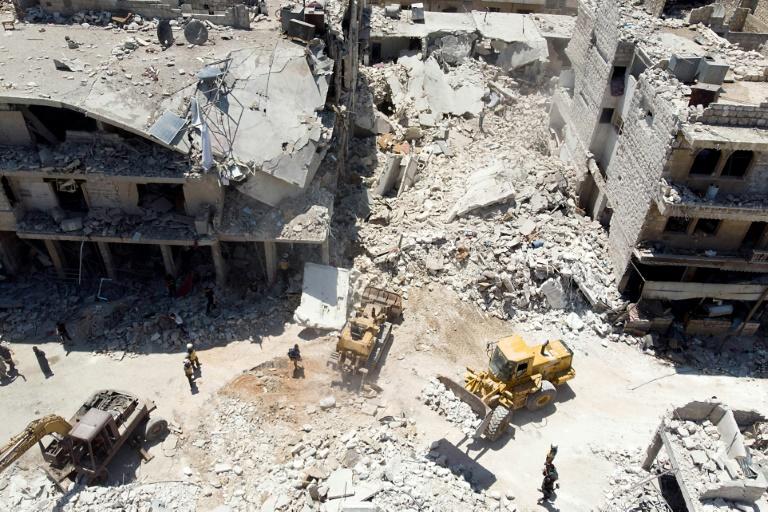 Les secouristes s'activent au pied d'un immeuble détruit par un bombardement, à Maaret al-Noomane, dans le nord-ouest de la Syrie, le 22 juillet 2019