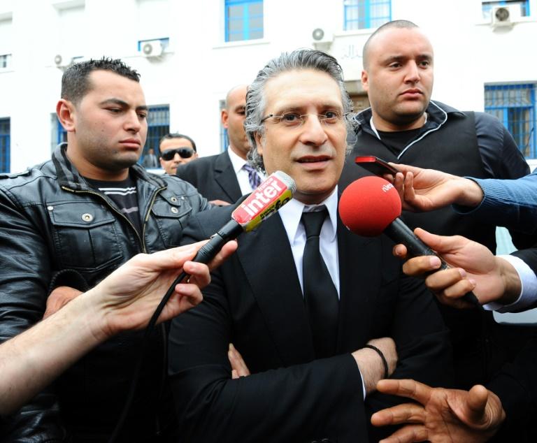Nabil Karoui (C), le fondateur de la chaîne de télévision tunisienne privée Nessma TV, sort d'un tribunal à Tunis, le 19 avril 2012