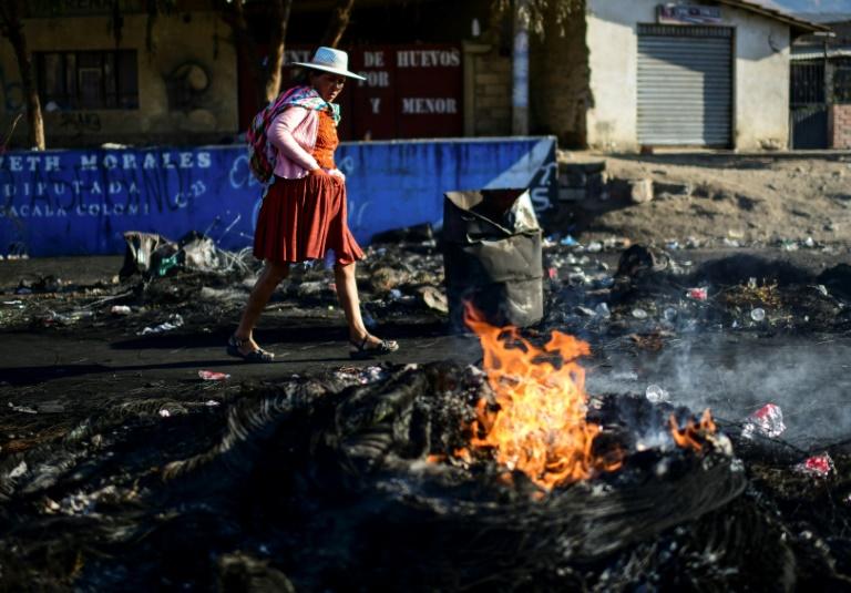 Une Améridienne marche le long d'une barricade levée par les partisans de l'ex-président bolivien Evo Morales dans la périphérie de Sacaba dans la province de Chapare, le 18 novembre 2019