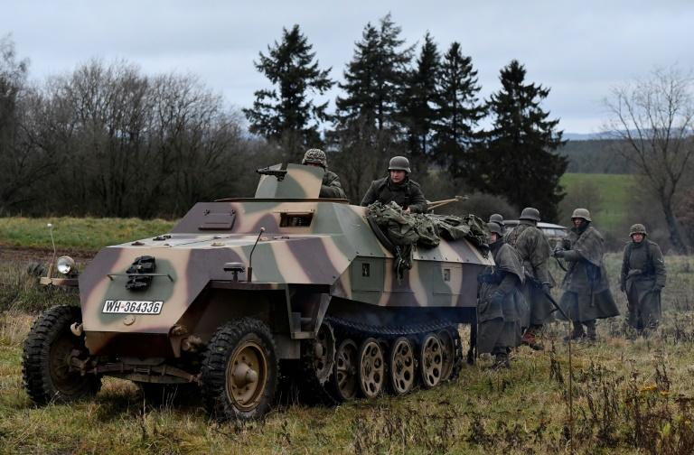 Des acteurs en uniformes de soldats allemands près d'un véhicule blindé participent à la reconstitution de la bataille des Ardennes à l'occasion du 75e nniversaire, le 12 décembre 2019 à Bastogne, en Belgique