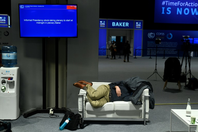 Un homme épuisé dort pendant les négociations finales de la COP25, dans la nuit du 14 au 15 décembre 2019 à Madrid
