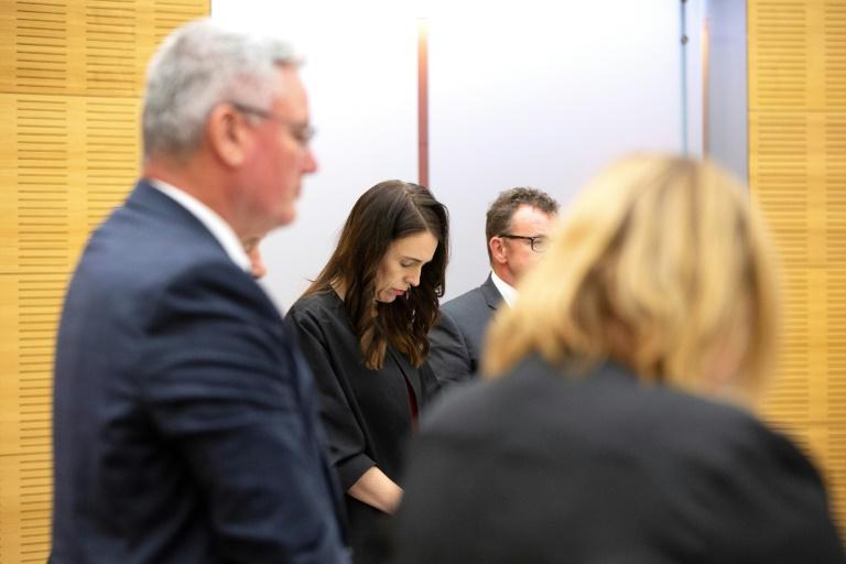 La Première ministre de Nouvelle-Zélande Jacinda Ardern (C) observe une minute de silence pour les victimes du volcan de White Island, au Parlement à Wellington le 16 décembre 2019