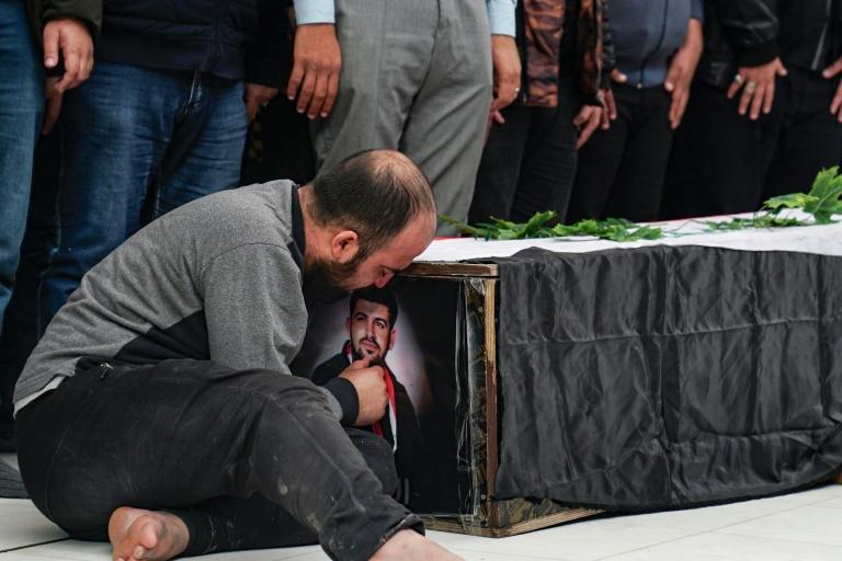 Un homme embrasse la photo d'un manifestant irakien et journaliste citoyen tué la veille à Bagdad, accrochée à son cercueil pendant ses funérailles à Najaf, au sud de Bagdad, le 7 décembre 2019