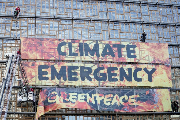 Des militants de Greenpeace évacués par des pompiers après avoir déployé une bannière sur le bâtiment du conseil européen à Bruxelles le 12 décembre 2019
