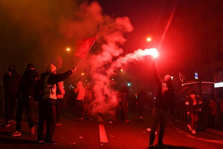 Un manifestant brandit une fusée rouge pendant la manifestation jeudi à Paris contre la réforme des retraites qui a vu des centaines de milliers de personnes descendre dans les rues