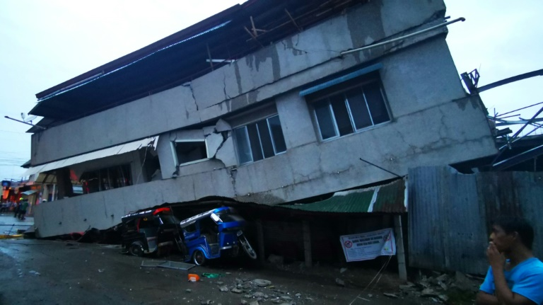 Des habitants observent une maison détruite avec un véhicule coincé dessous après un puissant séisme, à Padada dans la province de Davao del Sur sur l'île de Mindanao aux Philippines le 15 décembre 2019