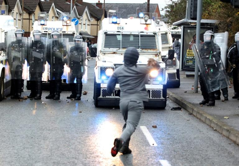 Un jeune homme lance des pierres sur des policiers à Belfast le 8 avril 2021