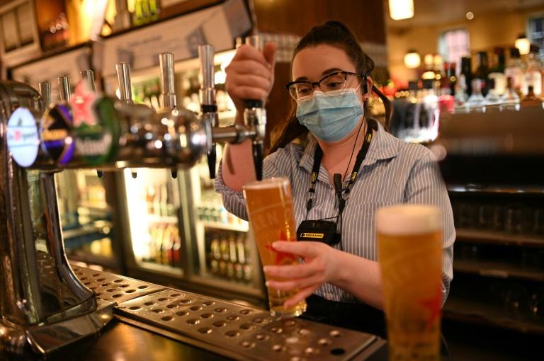 Photo d'archive prise le 22 octobre 2020 montrant une membre du personnel en train de servir une bière dans un bar à Manchester