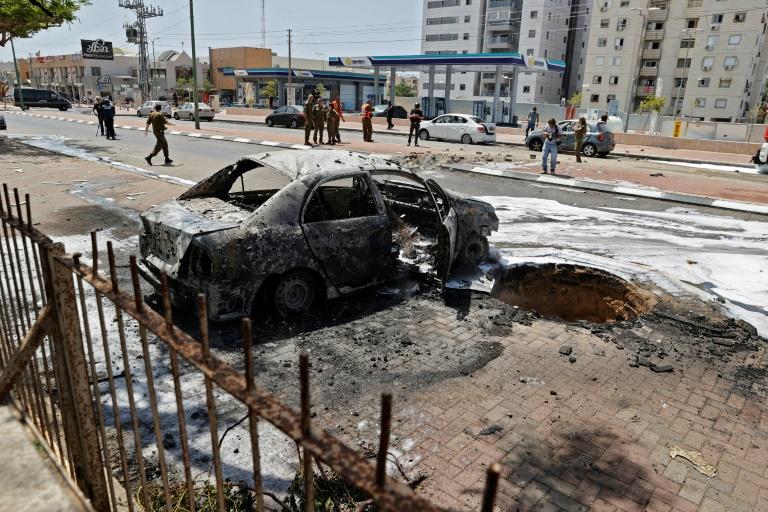 Photo prise le 11 mai 2021 montrant un véhicule détruit dans la ville israélienne d'Ashkelon, cible d'attaques à la roquette depuis la bande de Gaza proche