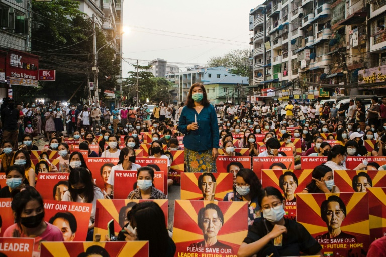 Des manifestantes à Rangoun le 12 mars 2021 brandissent des pancartes portant l'image de la cheffe du gouvernement civil renversée par un coup d'Etat et détenue.