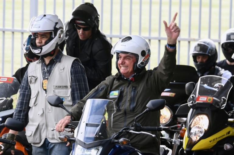 Le président brésilien Jair Bolsonaro salue ses partisans en moto le 9 mai 2021 à Brasilia