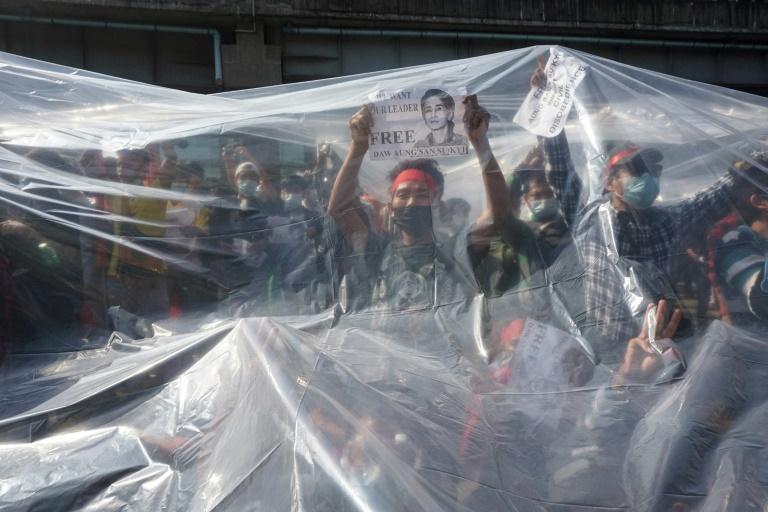 photo prise le 9 février 2021 montrant des manifestants en Birmanie sous un plastique les protégeant des canons à eau de la police à Rangoun