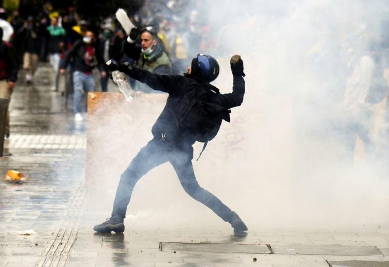 Un manifestant lance une pierre sur des policiers anti-émeutes à Bogota le 5 mai 2021.