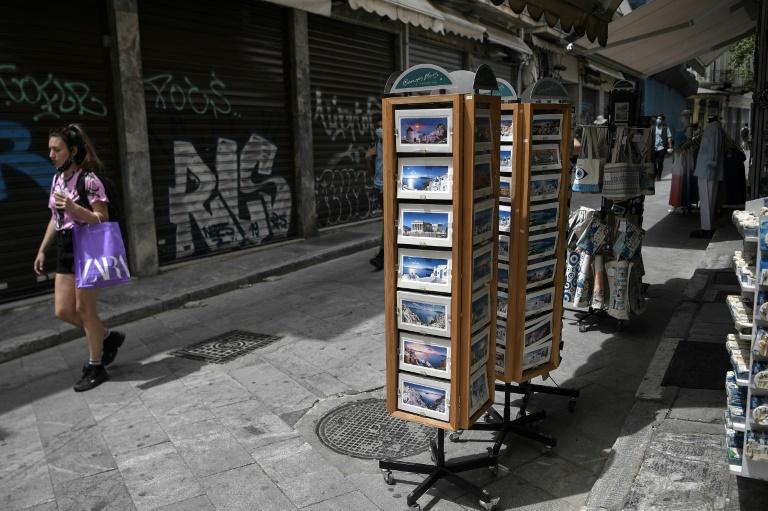 Une femme passe près d'une boutique de souvenirs dans le centre d'Athènes, le 12 mai 2021