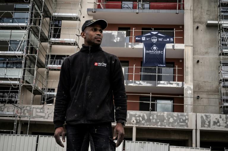 Le défenseur de Rumilly-Vallières, Houssame Boinali, pose devant la résidence en construction à Rumilly où il travaille, avant d'aller à l'entraînement, le 11 mai 2021 au stade d'Annecy, où aura lieu, dans deux jours, la demi-finale de la Coupe de France contre Monaco