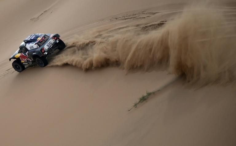 La Mini pilotée par Stéphane Peterhansel fend les dunes du Dakar en direction de Yanbu, en Arabie saoudite, le 14 janvier 2021