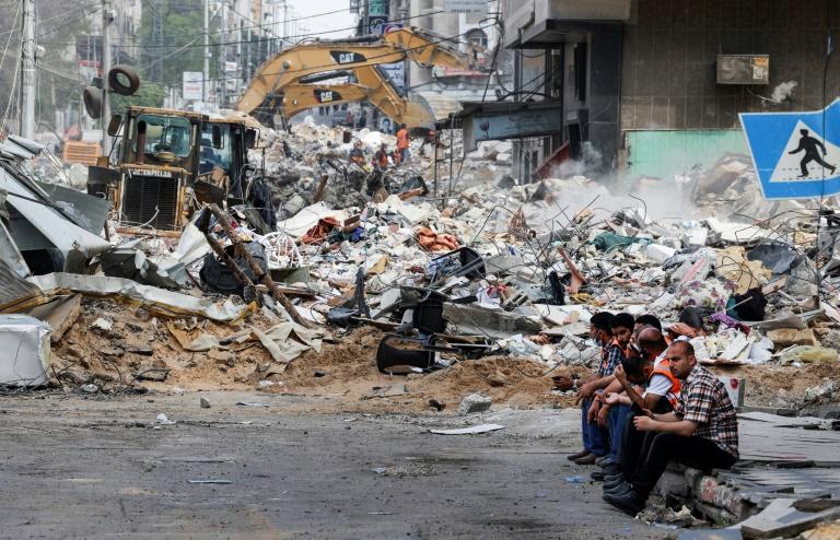 Des pelleteuses déblaient des débris dans les rues de Gaza après des bombardements israéliens, le 16 mai 2021
