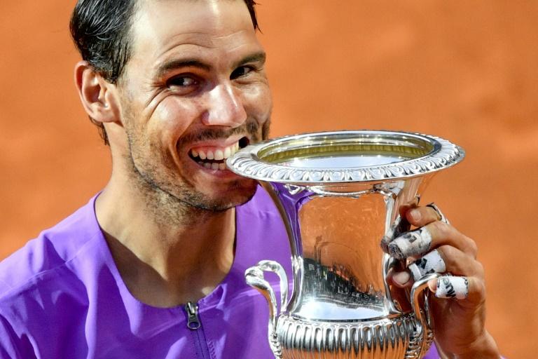 L'Espagnol Rafael Nadal mord son trophée du Masters 1000 de Rome après sa victoire en finale sur le Serbe Novak Djokovic, le 16 mai 2021