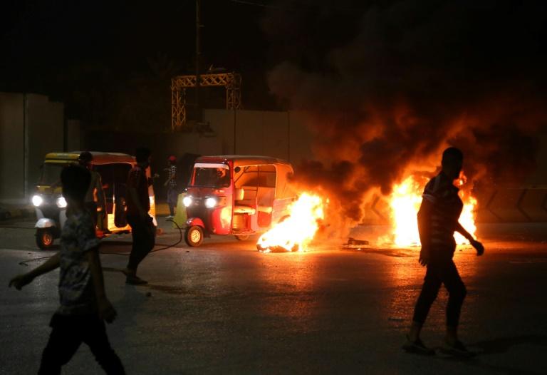 Des manifestants irakiens brûlent des pneus devant le siège du gouvernorat de Kerbala, la ville sainte chiite au sud de Bagdad, tôt le 9 mai 2021, à la suite de l'assassinat d'un militant anti-pouvoir