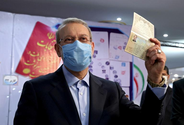 L'ancien président du Parlement Ali Larijani montre son passeport alors qu'il enregistre sa candidature à la présidentielle iranienne, de juin au ministère de l'Intérieur à Téhéran, le 15 mai 2021