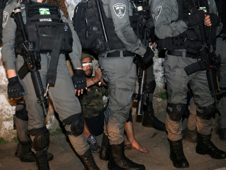 Un manifestant palestinien aux yeux bandés et entouré de membres des forces de sécurité israéliennes dans le quartier de Cheikh Jarrah à Jérusalem-Est, où des familles palestiniennes risquent d'être évincées, le 5 mai 2021