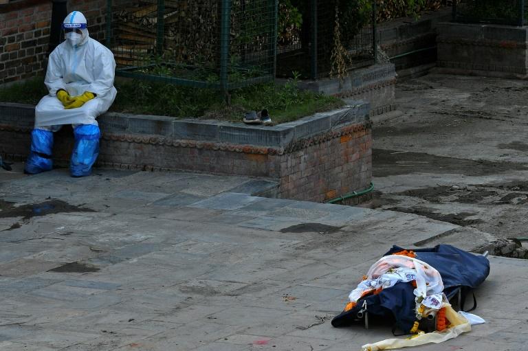 Un soignant, vêtu d'une tenue de protection sanitaire, près du corps d'une victime du Covid-19 en passe d'être transporté dans un crématorium, à Katmandou (Népal), le 14 mai 2021