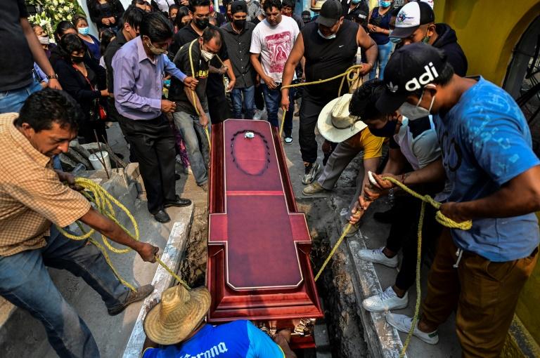 Des proches d'une victime de l'effondrement d'un pont, au passage d'un métro aérien à Mexico, l'enterrent le 5 mai 2021.