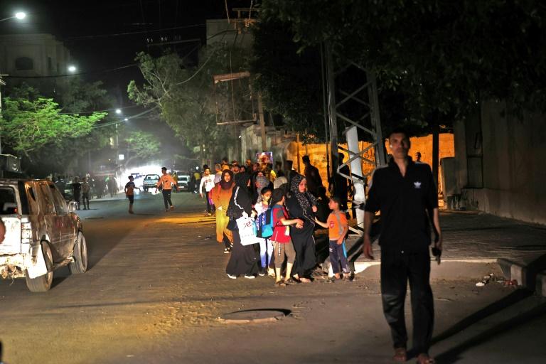 Des familles palestiniennes dans la rue après avoir évacué leurs maisons dans la bande de Gaza à la suite de violents bombardements israéliens, le 13 mai 2021