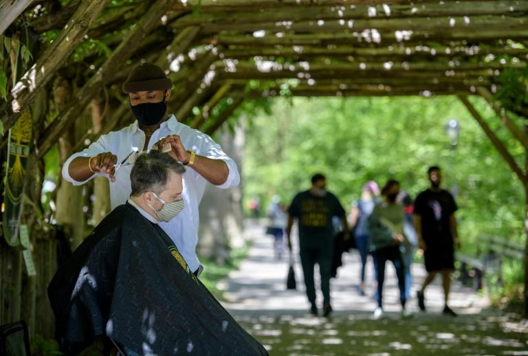 Le coiffeur de Central Park, Herman James, coupe les cheveux d'un client à Central Park, à New York, le 6 mai 2021
