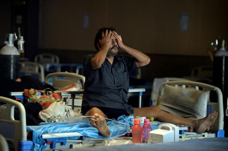 Un patient atteint du Covid-19 est assis sur un lit dans une salle de banquet transformé en centre de soins temporaire à New Delhi le 10 mai 2021
