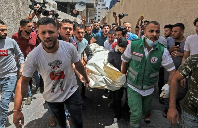 Des Palestiniens évacuent une personne d'un bâtiment visé par des frappes israéliennes à Gaza le 11 mai 2021