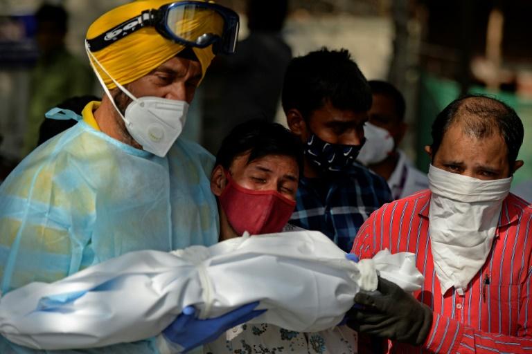 Des proches portent le corps d'un enfant décédé du Covid-19 dans un crématorium, le 12 mai 2021 à New Delhi, en Inde
