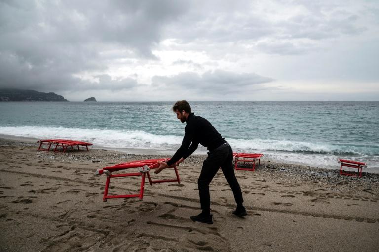 Un plagiste installe des chaises longues sur une plage à Noli, près de Gênes en Italie, le 16 mai 2021 pour le début de la saison