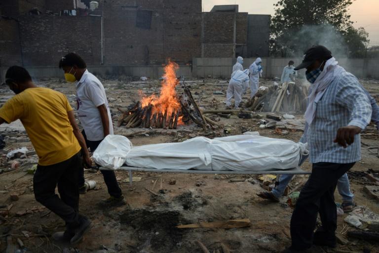Des proches assistent à la crémation d'une personne décédée du Covid-19 au crematorium de New Delhi le 11 mai 2021