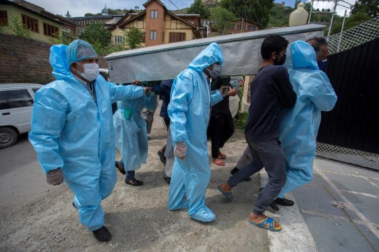 Des proches revêtus de combinaisons de protection portent le corps d'une victime du coronavirus lors de funérailles à Srinagar, Inde, le 7 mai 2021