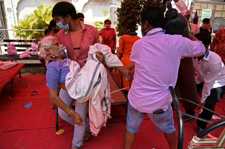 Un membre de la famille d'une malade atteinte du Covid la porte dans une tente à Ghaziabad en Inde le 4 mai 2021